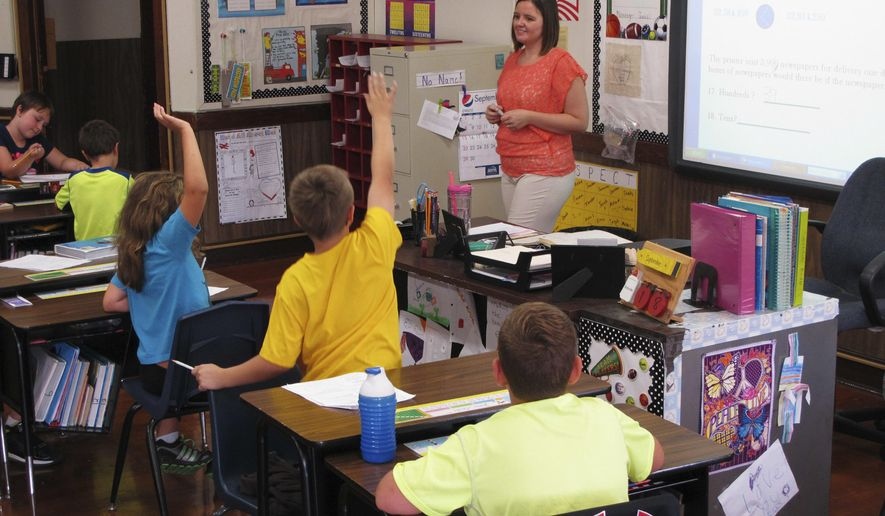 In this Sept. 18, 2013, photo, Shelly Ellis teaches fourth-grade students in a newly air conditioned classroom at Bement Elementary School in Bement, Ill. (AP Photo/David Mercer, File)