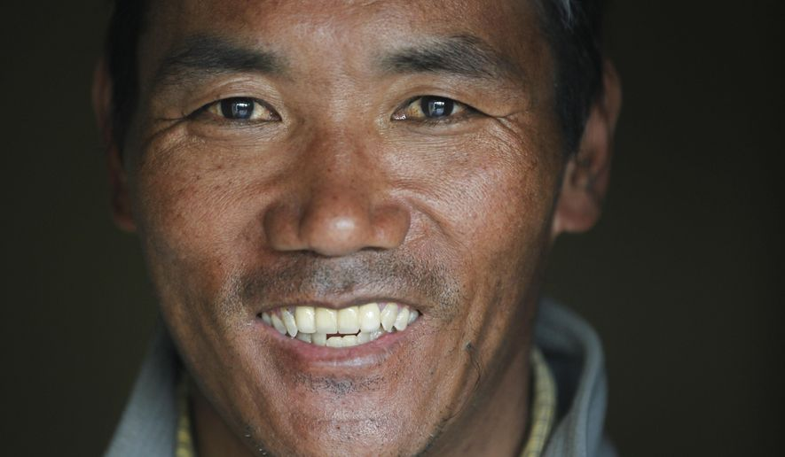 In this March 26, 2018 photo, Nepalese veteran Sherpa guide, Kami Rita, 48, poses for a photograph at his rented apartment in Kathmandu, Nepal.  Rita, who is one of just three people to scale Mount Everest 21 times, is about to attempt a record-breaking 22nd summit. (AP Photo/Niranjan Shrestha)