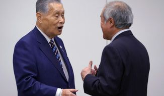 Tokyo 2020 Olympics President Yoshiro Mori, left, talks with Shunichi Suzuki, minister of the Tokyo 2020 Olympic and Paralympic Games, during an executive board meeting in Tokyo, Tuesday, April 10, 2018. Tokyo Olympic organizers said the Olympic flame will be put on display at various locations in the Tohoku region to help underscore Japan's recovery from the disaster that took more than 18,000 lives and triggered meltdowns at the Fukushima nuclear power plant. (AP Photo/Shizuo Kambayashi)