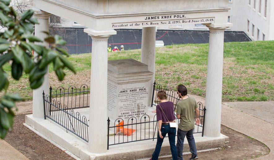FILE - In a March 24, 2017 file photo, visitors look at the burial place of President James K. Polk and his wife, Sarah Polk, on the grounds of the state Capitol in Nashville, Tenn. The body of former president James K. Polk has been moved three times since he died of cholera in 1849, and now an effort to move it again has taken on a life of its own in the Tennessee Legislature. A much-debated resolution urging that his remains be moved to a fourth resting place appeared dead in March 2018, but was resurrected before winning final approval Monday night, April 9, 2018, in the House. (AP Photo/Erik Schelzig, File)