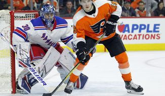 New York Rangers goalie Henrik Lundqvist, left, and Philadelphia Flyers' Nolan Patrick watch the puck shot by Claude Giroux head towards the net for a goal during the second period of an NHL hockey game Saturday, April 7, 2018 in Philadelphia, PA. (AP Photo/Tom Mihalek)