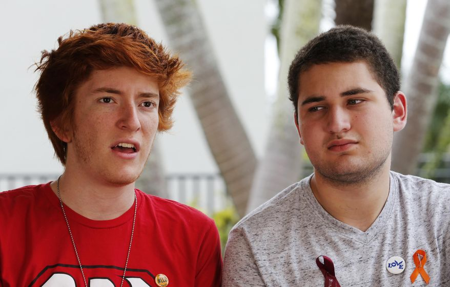 In this March 30, 2018, photo, Marjory Stoneman Douglas High School students Ryan Deitsch, left, and Alex Wind, talk during an interview with The Associated Press in Parkland, Fla. The students, along with others, are traveling around the country to talk about gun control. (AP Photo/Joe Skipper)