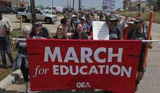 Demonstrators walk along NE 36th St. in the final leg of a 110 miles trip from Tulsa to the state Capitol as protests continue over school funding, in Oklahoma City, Tuesday, April 10, 2018. (AP Photo/Sue Ogrocki)