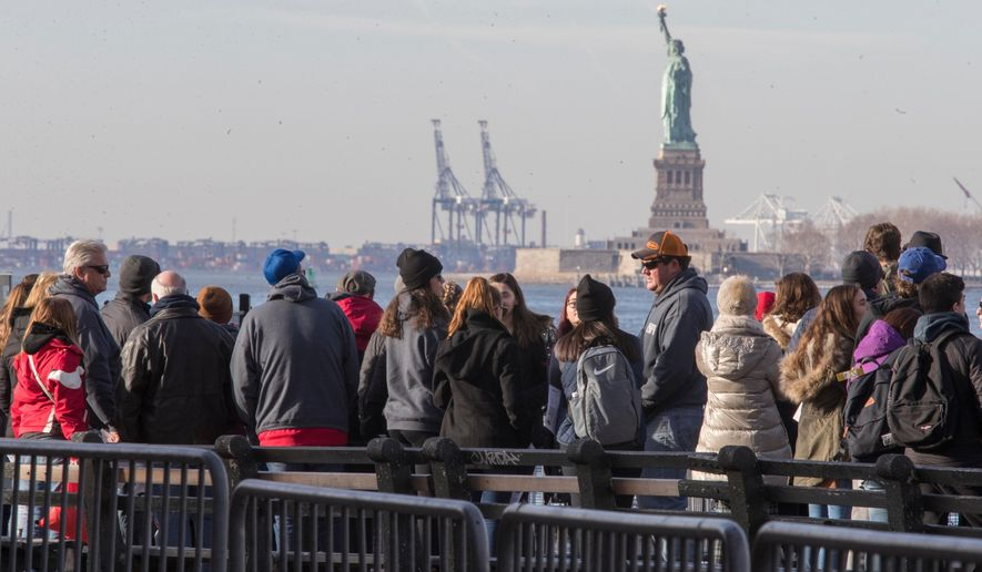 "FILE - In this Jan. 20, 2018, file photo, visitors to the Statue of Liberty stand in line to board a ferry that will cruise the bay around the statue and Ellis Island in New York. The U.S. Department of Commerce says government statistics showing a decrease in international arrivals may be wrong. The department is suspending publication of the data until it can be revised. Critics have been complaining of a ""Trump slump"" in international tourism, and arrivals data compiled by the government had validated those concerns until now. The Commerce Department says some international arrivals may have been miscategorized as U.S. residents, leading to an undercount. (AP Photo/Mary Altaffer, File)"