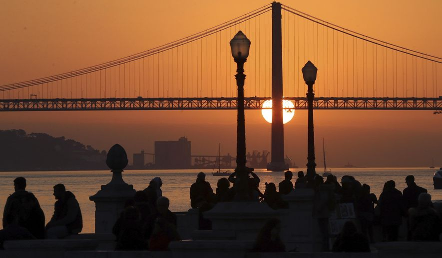 FILE - In this Feb. 5, 2016, file photo, people gather at Lisbon's Comercio square to watch the sun set behind the April 25th Bridge. A new tour company called Off the Grid, that asks participants to put their cellphones away, is launching with a trip to Lisbon in July. (AP Photo/Armando Franca, File)
