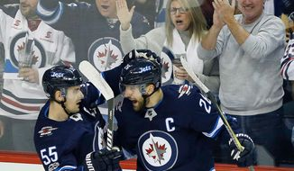FILE - In this Oct. 29, 2017, file photo, Winnipeg Jets center Mark Scheifele (55) and right wing Blake Wheeler (26) celebrate Wheeler's goal against the Pittsburgh Penguins during the first period of an NHL hockey game in Winnipeg, Manitoba. Captain Blake Wheeler will lead the Jets against the Minnesota Wild in Game 1 of a first round playoff series on Wednesday, April 11, 2018, in Winnipeg. (John Woods/The Canadian Press via AP, File)