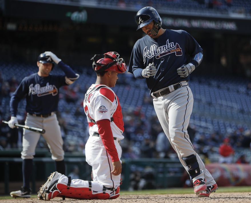 Atlanta Braves Kurt Suzuki (24) crosses home as Washington Nationals catcher Pedro Severino (29) watches, after hitting a solo homer in the 11th inning of a baseball game at Nationals Park, Wednesday, April 11, 2018 in Washington. Waiting on the on-deck circle is Braves Peter Bourjos (12), Atlanta won 5-3. (AP Photo/Pablo Martinez Monsivais)