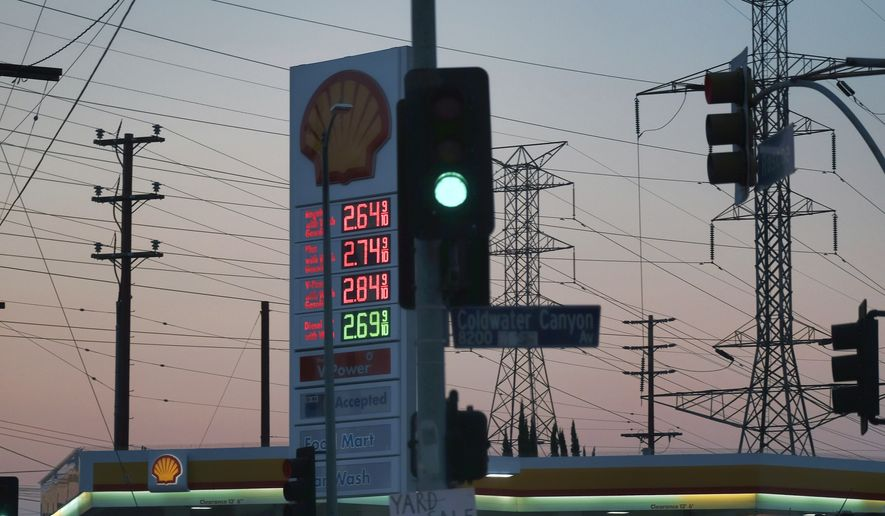 In this file photo, high tension power lines are seen behind a Shell gas station displaying fuel prices, early morning on Thursday, Aug. 25, 2016. (AP Photo/Richard Vogel) **FILE**