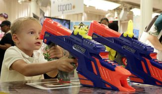 "In this file photo, a 5-year-old child plays with Hasbro's ""Nerf Nitro MotoFury Rapid Rally,"" at the TTPM Holiday Showcase, in New York, Tuesday, Sept. 26, 2017. In April 2018 the toy company announced a pilot toy-recycling program designed to recycle plastics from discarded toys to be repurposed to make playground equipment and park benches. (AP Photo/Richard Drew) **FILE**"