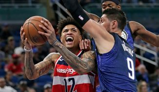 Washington Wizards' Kelly Oubre Jr. (12) goes up for a shot against Orlando Magic's Nikola Vucevic (9) during the first half of an NBA basketball game, Wednesday, April 11, 2018, in Orlando, Fla. (AP Photo/John Raoux)