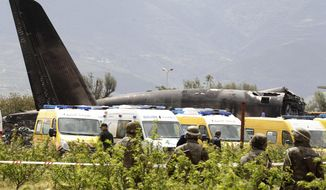 Algerian soldiers watch the military plane after it crashed in Boufarik, near the Algerian capital, Algiers, Wednesday, April 11, 2018. Algerian emergency services say 181 people have been killed in a military plane crash and some survivors have been rescued. (AP Photo/Anis Belghoul)