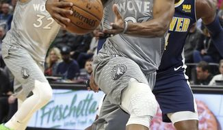 Minnesota Timberwolves' Jimmy Butler, left, drives as Denver Nuggets' Paul Millsap, right, defends during the first half of an NBA basketball game Wednesday, April 11, 2018, in Minneapolis. (AP Photo/Jim Mone)