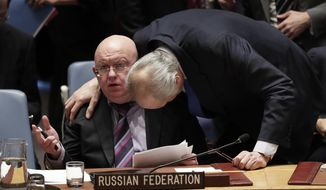 Russian Ambassador to the United Nations Vasily Nebenzya talks with Syrian Ambassador to the United Nations Bashar Ja'afari, during a Security Council meeting, Tuesday, April 10, 2018, at United Nations headquarters. (AP Photo/Julie Jacobson)