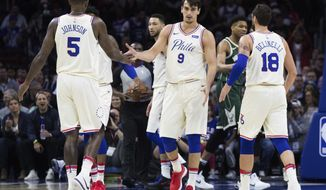 Philadelphia 76ers' Dario Saric, center, of Croatia, celebrates with Marco Belinelli, right, of Italy, and Amir Johnson, left, during the first half of an NBA basketball game against the Milwaukee Bucks, Wednesday, April 11, 2018, in Philadelphia. (AP Photo/Chris Szagola)