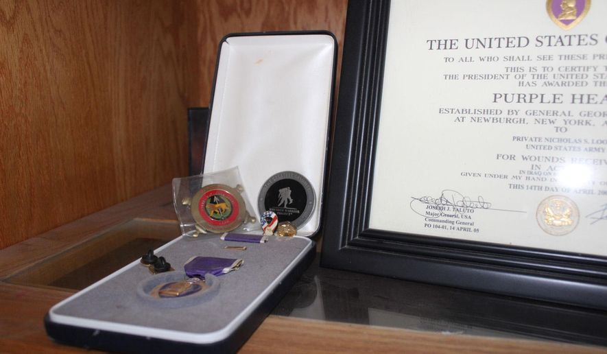 A Purple Heart medal, given to military members who are injured in combat, is on display inside Nick Loomis' Racine home. He and his wife started CM Skullies, a product that keeps his head warm while wearing sunglasses when he rides his motorcycle, and tested a handful of designs before finding a quality prototype. Last September, the couple acquired a patent.  (Adam Rogan/The Journal Times via AP)