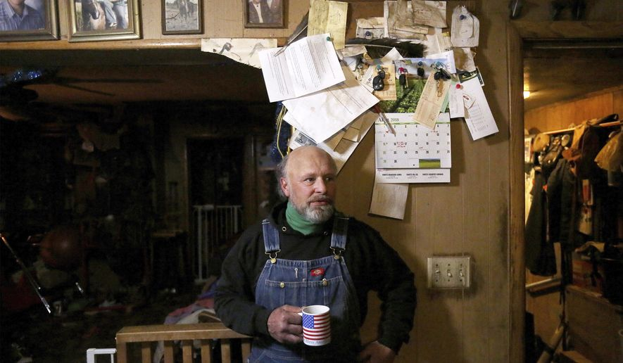 Pictured in the Rudolph, Wis. farm house in Junction City, where he was born and raised in, Carl Flaig reflects on the transition his family has made from a dairy operation to an organic farm and aquaponics business Thursday, April 5, 2018. In the fields of his property also reside several blinds, which Flaig built to offer a viewing vantage for birding enthusiasts who arrive each year to view the spring mating rituals of prairie chickens. (John Hart/Wisconsin State Journal via AP)