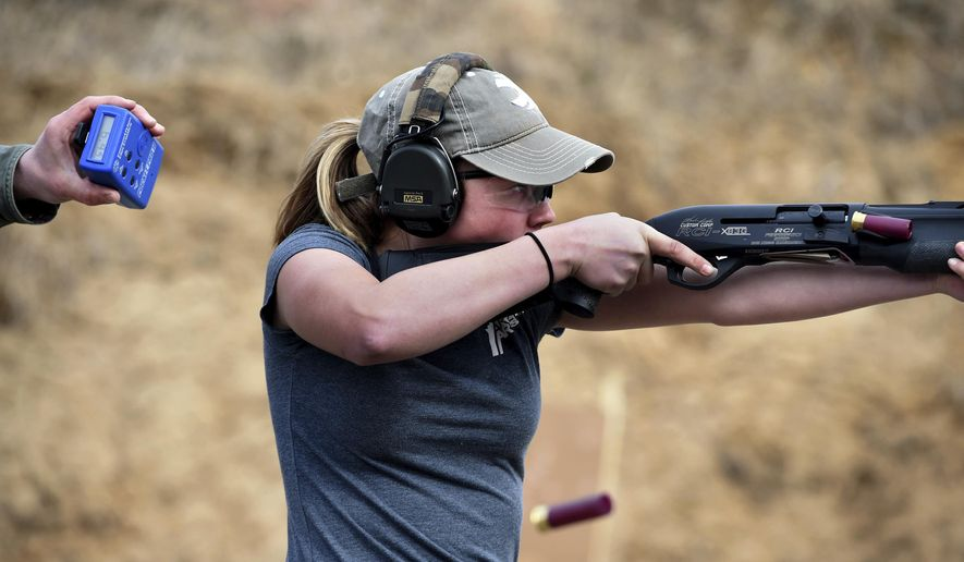 In a Friday, March 23, 2018 photo, Dakota Overland, 14, a competitive shooter who travels to meets across the nation, is timed by her father, Todd, during a training session at a gun range in Forest Lake, Minn. During a 3-gun match, a shooter moves through different stages of a course, engaging targets in a variety of different positions. The stage might require the use of a shotgun, rifle or pistol and the shooter will need to transition between them. (Jean Pieri/Pioneer Press via AP)