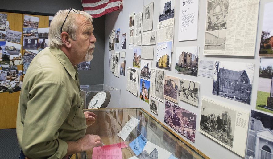 In this April 3, 2018, photo, Doug Krueger, the facilities maintenance director for Nicollet county, looks over photos of the St. Peter tornado damage at the Nicollet County Historical Society exhibit in Mankato, Minn. Krueger loaned a clock from the second floor of the Nicollet County Courthouse (back) to the exhibit that is stopped at 5:29, the time the power went out due to the tornado. (Jackson Forderer/The Free Press via AP)
