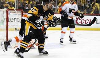 Pittsburgh Penguins' Sidney Crosby (87) redirects a shot past Philadelphia Flyers goaltender Brian Elliott for a goal during the second period in Game 1 of an NHL first-round hockey playoff series in Pittsburgh, Wednesday, April 11, 2018. (AP Photo/Gene J. Puskar)