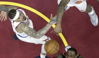 Cleveland Cavaliers' LeBron James, bottom, drives to the basket against New York Knicks' Michael Beasley, left, and Kyle O'Quinn in the first half of an NBA basketball game, Wednesday, April 11, 2018, in Cleveland. (AP Photo/Tony Dejak)