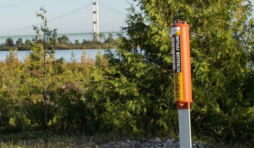 FILE - In this Sept. 23, 2015, file photo, the Mackinac Bridge is visible from a marker near Enbridge Line 5 on the northern shore of the Straits of Mackinac in Michigan. Michigan Gov. Rick Snyder said Wednesday, April 11, 2018, that twin oil pipelines beneath the waterway linking two of the Great Lakes apparently were damaged by the same vessel believed to have caused a recent 600-gallon coolant fluid leak from electric cables. Snyder said that Enbridge Inc. had notified the state about the damage to its Line 5 pipes, saying it was minor and consisted of three small dents. (Neil Blake /The Grand Rapids Press via AP, File)