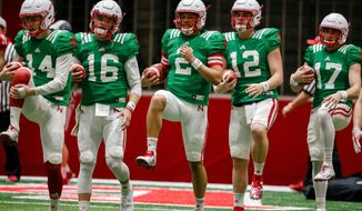 FILE - In this April 3, 2018, file photo, Nebraska quarterbacks Tristan Gebbia (14), Noah Vedral (16), Adrian Martinez (2), Patrick O'Brien (12) and Andrew Bunch (17), warm up during NCAA college football spring training in Lincoln, Neb. Spring practice is just past the midway point at Nebraska, and new coach Scott Frost is beginning to flesh out a quarterback pecking order.  (AP Photo/Nati Harnik, File)