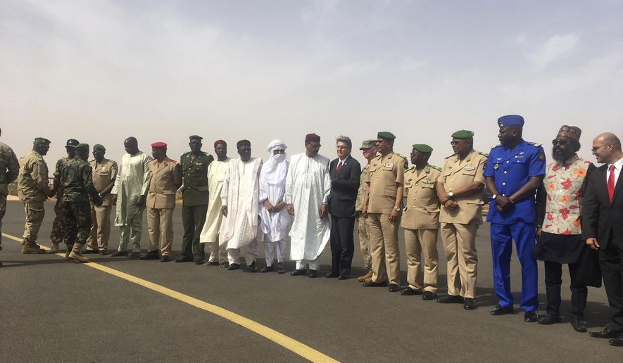 U.S Ambassador to Niger, Eric P. Whitaker, centre, and Niger's Minister of Defense Kalla Moutari, stand with other government officials for a photograph during an open annual counter-terror exercise in Niamey, Niger, Wednesday, April 11, 2018. Six months after the deaths of U.S. soldiers in Niger led to questions about the military's presence in the West African nation, the U.S. special operations command in Africa on Wednesday opened its annual counter-terror exercise in the face of a growing extremist threat. (AP Photo/Carley Petesch)