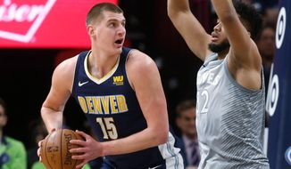 Denver Nuggets' Nikola Jokic of Serbia, left, eyes the basket as Minnesota Timberwolves' Karl-Anthony Towns defends during the first half of an NBA basketball game Wednesday, April 11, 2018, in Minneapolis. (AP Photo/Jim Mone)