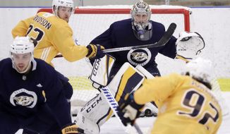 Nashville Predators goalie Pekka Rinne, of Finland, defends the net as left wing Viktor Arvidsson (33), of Sweden, sets up in front of him during a practice Monday, April 9, 2018, in Nashville, Tenn. The Predators are scheduled to play the Colorado Avalanche in the first round of the NHL Western Conference hockey playoffs on Thursday. (AP Photo/Mark Humphrey)
