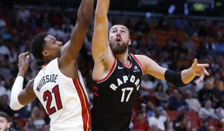 Toronto Raptors center Jonas Valanciunas (17) goes up for a shot against Miami Heat center Hassan Whiteside (21) during the first half of an NBA basketball game Wednesday, April 11, 2018, in Miami. (AP Photo/Wilfredo Lee)