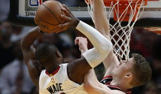 Miami Heat guard Dwyane Wade (3) goes up for a shot against Toronto Raptors center Jakob Poeltl (42) during the first half of an NBA basketball game Wednesday, April 11, 2018, in Miami. (AP Photo/Wilfredo Lee)