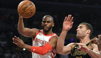 Houston Rockets guard Chris Paul, left, passes the ball as Los Angeles Lakers center Brook Lopez defends during the first half of an NBA basketball game Tuesday, April 10, 2018, in Los Angeles. (AP Photo/Mark J. Terrill)