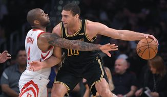 Houston Rockets forward PJ Tucker, left, reaches for the ball held by Los Angeles Lakers center Brook Lopez during the first half of an NBA basketball game Tuesday, April 10, 2018, in Los Angeles. (AP Photo/Mark J. Terrill)