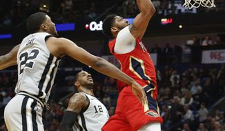 New Orleans Pelicans forward Anthony Davis (23) drives to the basket past San Antonio Spurs forward Rudy Gay (22) and forward LaMarcus Aldridge (12) in the first half of an NBA basketball game in New Orleans, Wednesday, April 11, 2018. (AP Photo/Scott Threlkeld)