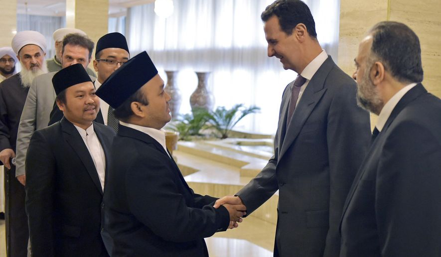 """This photo released by the Syrian official news agency SANA, shows Syrian President Bashar Assad, second right, greeting a delegation of Muslim clerics from around the world, who took part in a two-day conference called, """"Unity of the Muslim World,"""" in Damascus, Syria, Wednesday, April 11, 2018. (SANA via AP)"""