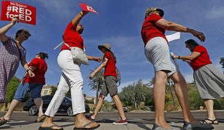 Arizona teachers protest their low pay and school funding in front of a local radio station waiting for Republican Gov. Doug Ducey to show up for a live broadcast Tuesday, April 10, 2018, in Phoenix. Arizona teachers are threatening a statewide walkout, following the lead of educators in other states. (AP Photo/Ross D. Franklin)