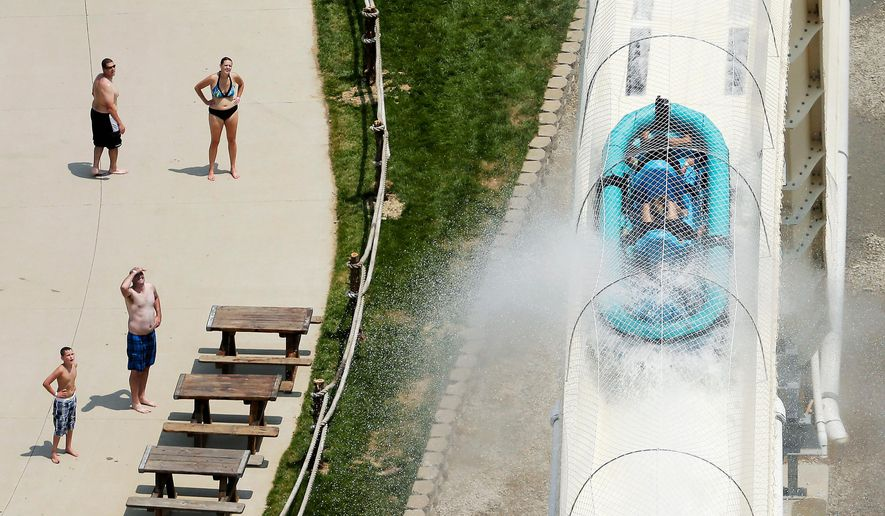 "FILE - In this July 9, 2014 file photo, riders are propelled by jets of water as they go over a hump while riding a water slide called ""Verruckt"" at Schlitterbahn Water Park in Kansas City, Kan. A lender on Monday, April 9, 2018, warned investors that criminal indictments stemming from the decapitation of a 10-year-old boy on the slide in 2016 at the park could hurt owner Schlitterbahn's chances of repaying a $174.3 million loan balance. (AP Photo/Charlie Riedel, File)"