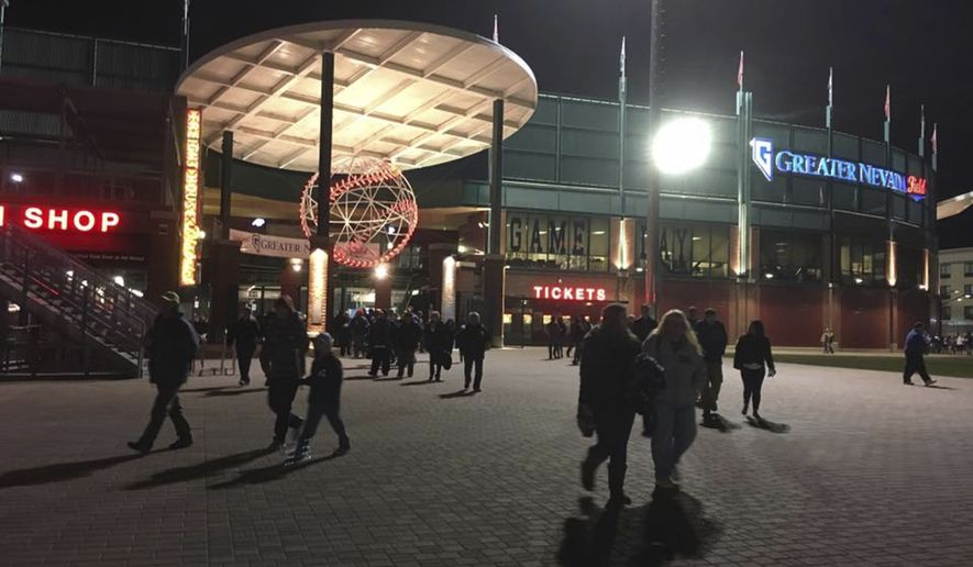 In this April 11, 2017 photo, fans walk outside Greater Nevada Field during last year's opening game for the Reno Aces minor league baseball team in Reno, Nev. A Nevada woman has declined an invitation to sign the national anthem at one of the Aces' games this summer because the team won't let her bring her gun. The woman said she wears the gun or keeps it in a purse because she doesn't feel safe walking at night in downtown Reno, where the stadium is located.  (AP Photo/Scott Sonner)