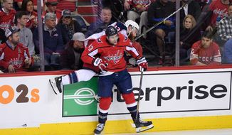 Washington Capitals right wing Tom Wilson (43) checks Columbus Blue Jackets defenseman Ian Cole (23) against the boards during the third period in Game 1 of an NHL first-round hockey playoff series, Thursday, April 12, 2018, in Washington. (AP Photo/Nick Wass)