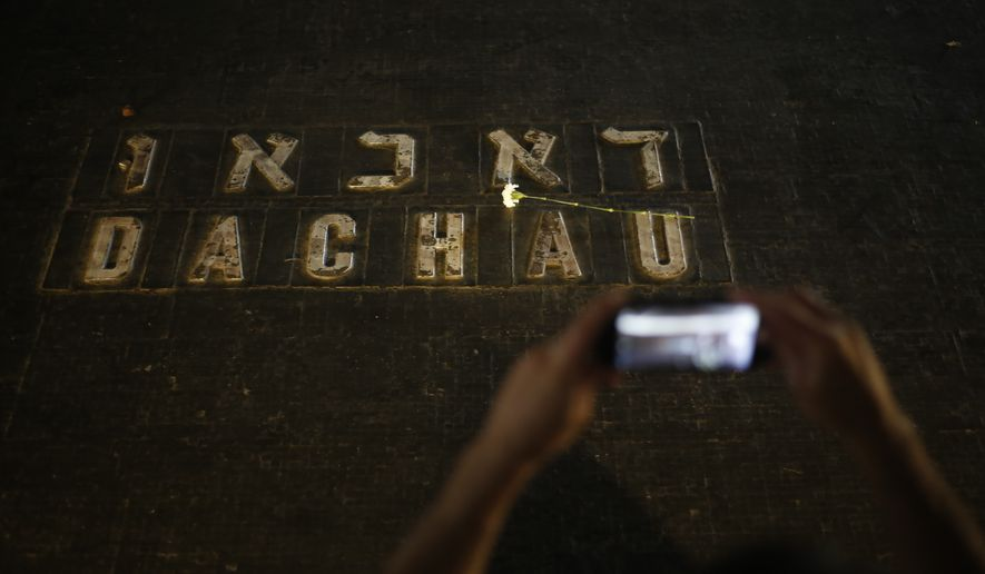 A man uses a mobile phone to photograph flowers placed on the names of concentration camps during the annual ceremony on Holocaust Remembrance Day at the Yad Vashem Holocaust Memorial in Jerusalem, Thursday, April 12, 2018. (AP Photo/Ariel Schalit)