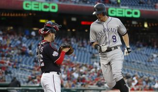 Colorado Rockies' DJ LeMahieu (9) crosses home after hitting a solo home run off Washington Nationals starting pitcher Gio Gonzalez as Nationals catcher Matt Wieters (32) watches during the first inning of a baseball game at Nationals Park, Thursday, April 12, 2018, in Washington. (AP Photo/Pablo Martinez Monsivais)