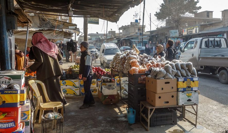 In the central marketplace of Qamishli, where the SDF and pro-Assad government forces share jurisdiction, merchants and customers are more concerned about the fluctuating value of the Syrian pound than about violent clashes. (Photo By Filip Warwick/Special to The Washington Times)