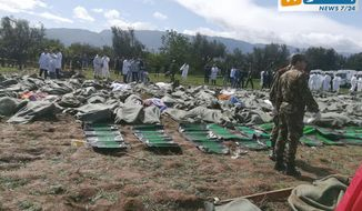 In this image from Algerian TV agency Ennahar TV, bodies are gathered near scene of a fatal military plane crash at Boufarik military air base near the Algerian capital, Algiers, Wednesday, April 11, 2018. An Algerian military plane carrying soldiers and their families crashed soon after takeoff Wednesday into a field in northern Algeria, killing more than 250 people in what appeared to be the North African nation's worst-ever plane crash. (Ennahar TV via AP)