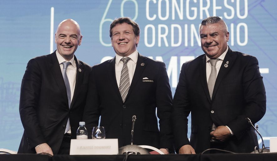 FIFA President Gianni Infantino, left, Dominguez, center, president of the South American Football Confederation, CONMEBOL, and Claudio Tapia, president of the Argentine Football Association, right, pose for a photo during CONMEBOL's annual conference in Buenos Aires, Argentina, Thursday, April 12, 2018. CONMEBOL has asked FIFA to expand the World Cup to 48 teams for the 2022 tournament in Qatar. (AP Photo/Martin Ruggiero)