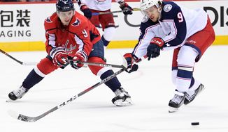 Washington Capitals defenseman Dmitry Orlov, left, of Russia, fights for the puck against Columbus Blue Jackets left wing Artemi Panarin, of Russia, during the second period in Game 1 of an NHL first-round hockey playoff series Thursday, April 12, 2018, in Washington. (AP Photo/Nick Wass)