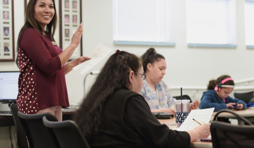 In this March 22, 2018, photo, Dalila Martinez goes through the agenda at the Caldwell School District's Migrant Education meeting in Caldwell, Idaho. (Chris Bronson/The Idaho Press-Tribune via AP)