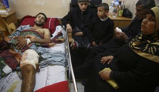 In this Monday, April 9, 2018 photo, Raed Jadallah, a Palestinian 25-year-old surfer, lies on a bed as his father, mother and brothers visit him, at the Shifa hospital in Gaza. Jadallah is among the nearly 1,300 people that Palestinian health officials said have been shot and wounded by Israeli soldiers during mass border protests over the past two weeks. The casualty figures are at the heart of an intensifying debate over the military's open-fire orders. (AP Photo/Adel Hana)