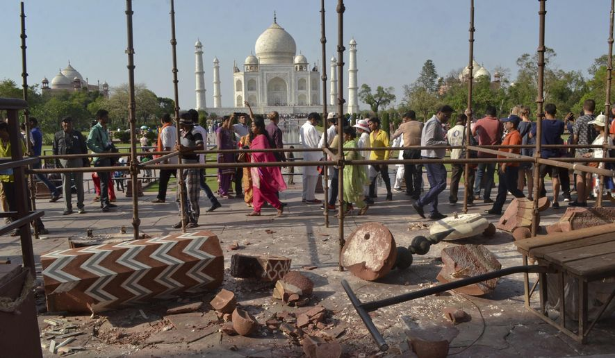 Tourists walk past the debris after a powerful storm Wednesday night toppled two minarets at the entry gates of the Taj Mahal monument in Agra, India, Thursday, April 12, 2018. (AP Photo/Pawan Sharma)