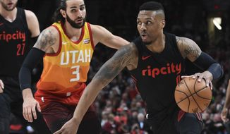 Portland Trail Blazers guard Damian Lillard, right, drives to the basket past Utah Jazz guard Ricky Rubio, left, during the first half of an NBA basketball game in Portland, Ore., Wednesday, April 11, 2018. The Blazers won 102-93. (AP Photo/Steve Dykes)