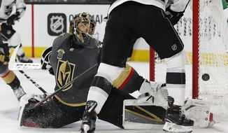 Vegas Golden Knights goaltender Marc-Andre Fleury blocks a shot next to Los Angeles Kings left wing Tanner Pearson during the third period of Game 1 of an NHL hockey first-round playoff series, Wednesday, April 11, 2018, in Las Vegas. The Golden Knights won 1-0. (AP Photo/John Locher)